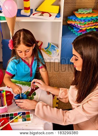 Small students with teacher painting in art school class. Child drawing by paints on table in kindergarten. Mom and daughter at home. Craft drawing education develops creative abilities of children.