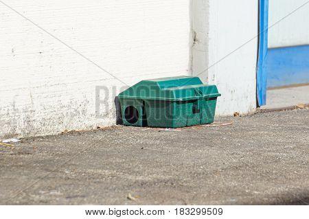 Poison rat trap box on floor near wall .