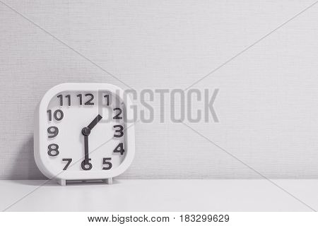 Closeup white clock for decorate show half past one o'clock or 1:30 p.m. on white wood desk and cream wallpaper textured background in black and white tone with copy space