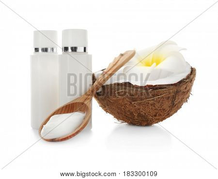 Fresh coconut, bottles with cream and wooden spoon on white background