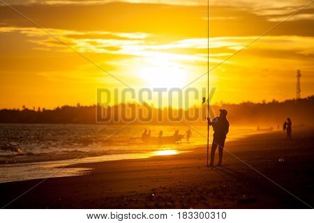 Silhouette of a girl on the beach with a fishing rod in summer, at sunset, fishermen pulling a boat ashore