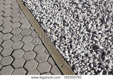 Grey colored round stones next to a concrete curb .