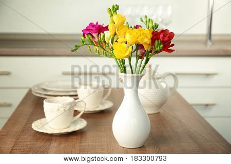 Vase with beautiful bouquet of freesia flowers on table in room