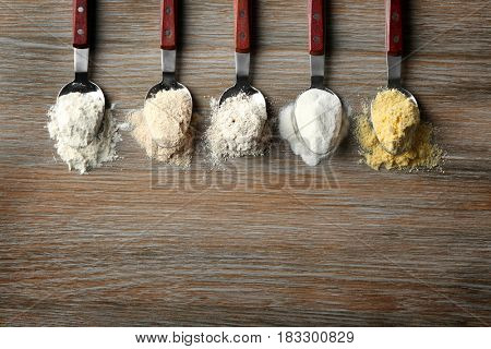 Spoons with different types of flour on wooden table