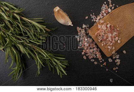 Salt, pepper, garlic and rosemary on a chopping board