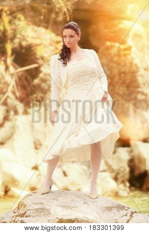 A beautiful bride stands on a rock in a mountain stream
