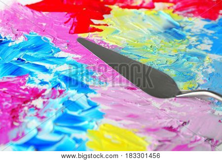 Colorful oil paint splashes and palette knife, closeup