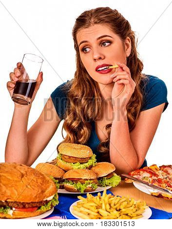 Woman eating french fries and hamburger. Student consume fast food on table. Girl drinks cola and dreams . Girl trying to eat junk. Advertise fast food on isolated.
