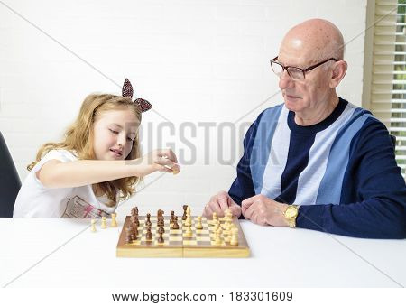 Grandfather is teaching his granddaughter to play chess, friends, game, grandfather, grandparent, happy, home,family, chess, play chess, grandfather and grandmother, friends, game, grandfather, grandparent, happy, together,