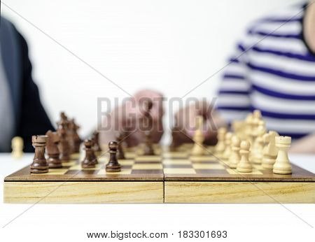 Grandfather and grandmother play chess , Defocusing, male and female hand move figures on a chessboard