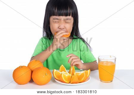 Asian Chinese Little Girl Eating Sour Orange And Making Grimace