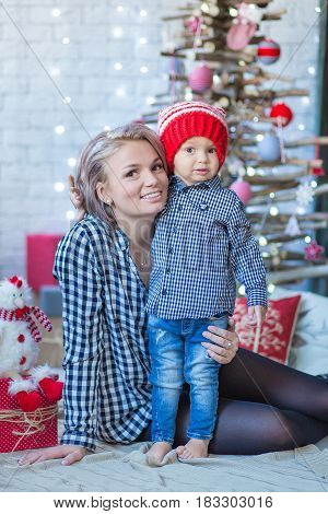 Portrait of happy mother and adorable baby celebrate Christmas. New Year's holidays. Toddler with mom in the festively decorated room with Christmas tree and decorations