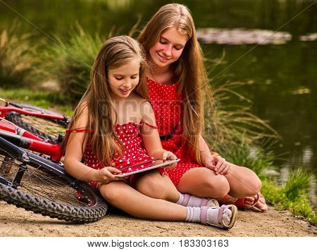 Mother and daughter on bicycle. Bikes cycling family. Happy mother and daughter are sitting on green grass road near bicycles.