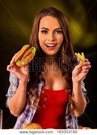 Woman eating french fries and hamburger. Portrait of student consume fast food on table. Girl trying to eat junk. Advertise fast food on daek background.