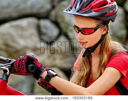 Woman on bicycle ride mountain. Girl with smart watch traveling in summer park. Cycling person with rucksack counts pulse after sport training. Sport trip is good for health and figure.