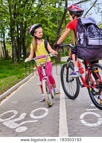 Bicycle path and sign with children. Girls wearing bicycle helmet with rucksack ciclyng ride. Kids are on white bike lane . Alternative to urban transport. Oncoming traffic.