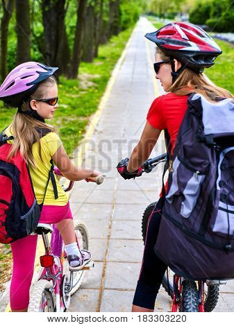 Bicycle path with children. Girls wearing bicycle helmet with rucksack ciclyng ride. Kids or mother with daughter are on yellow bike lane . Alternative to urban transport. Back view.