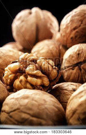 Walnuts. On a black background. Rustic. Fresh autumn walnut harvest in the village