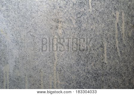 Grungy gray concrete wall with whitewash and vertical lines.