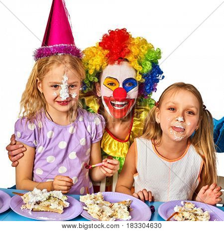Birthday children clown eating cake with two girl together. Kids with messy face have tier cake fight on isolated. Fun happy childhood of small group people.