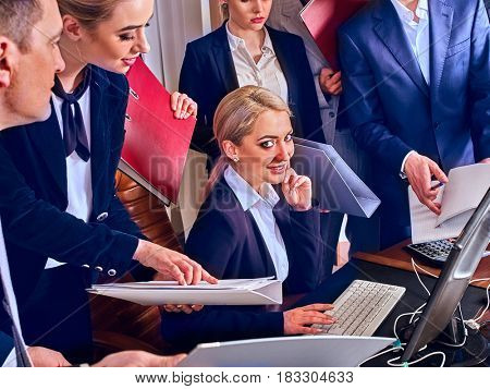 Business people office life of team people working with papers sitting table . Cabinets with folders and jalousie background. Woman boss is satisfied with her supervisory work.