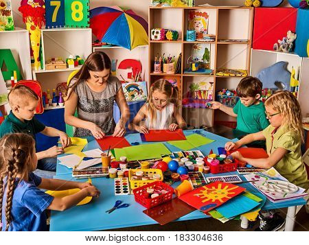 School children with scissors and cutting color paper . Kids and teacher in class room. Development and social lerning . Children's project in kindergarten. Large group girls and boys together.