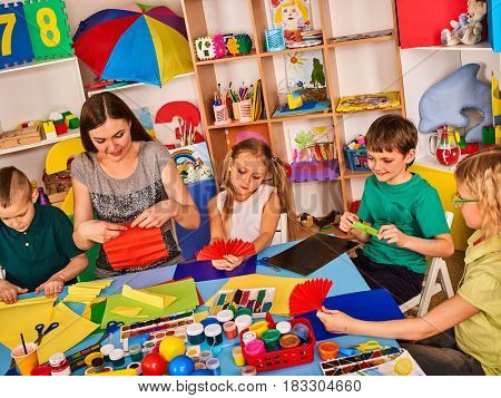 School children with scissors in kids hands cutting paper with teacher in class room. Development and social lerning . Children's project in kindergarten. Large group girls and boys together.