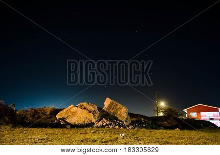 Rock in the night accompanied by rocks