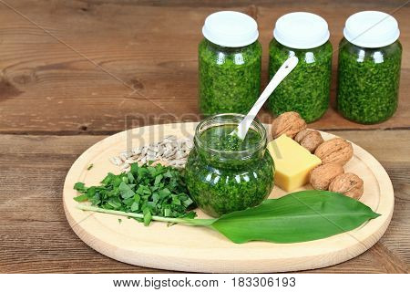 Homemade pesto in jars on rustic wooden board. Made from wild garlic olive oil cheese and walnuts.