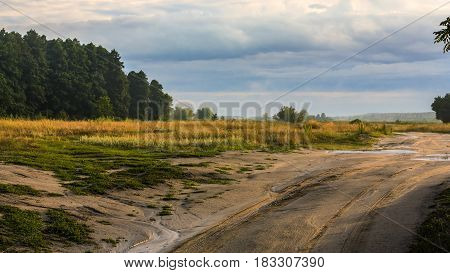 Rural evening landscape with trees and sky after rain