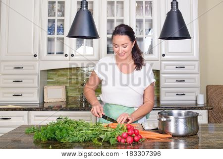 Attractive positive woman cutting vegetables -radish, carrots, greens - in her sunny kitchen, smiling happily