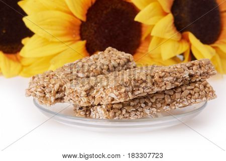 Sunflowers and dish with pressed sunflower seeds candied in sweet syrup on a white background. Sweet dessert.