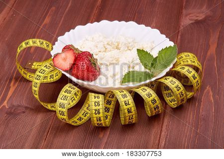 Natural cottage cheese with fresh ripe strawberries, leaf of mint and measuring tape on a wooden table. Healthy eating concept. Dieting and slimming.