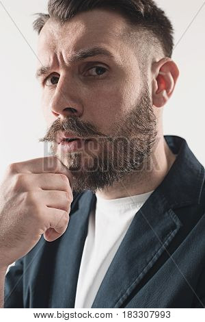 Young attractive suspicious macho stylish fashionable guy. Portrait on white background. Concept of suspicious
