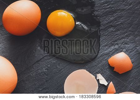 Fresh chicken brown home eggs with cracked eggshell and yolk on rustic slate black background. Closeup. Natural healthy food and organic cooking ingredients