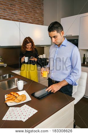 Young couple looking news in their electronic devices while having fast breakfast in home before go to work