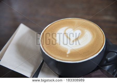 latte art heart shape coffee top view on wooden table background at coffe shop
