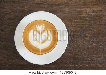 Coffee cup latte art with hearth shape foam top view on wooden table background in coffee shop