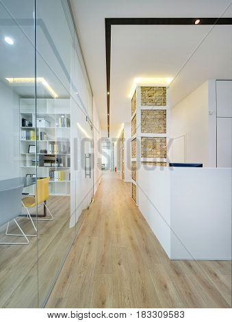 Hall with glowing lamp in the office in a modern style. There are white and brick walls, work zone with a glass partition and a door, table with chairs, reception desk, corridor, parquet on the floor.