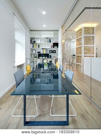 Work zone with white walls, glass partition with a door, parquet on the floor. There is a big dark specular table with gray and yellow chairs, shelves with folders, books, frames, boxes and plants.