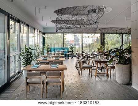 Stylish modern cafe with large windows and a parquet on the floor. There are many tables with glasses and plates,  chairs, sofa, plants in the concrete pots, several metal reticulated constructions.