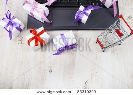 Shopping Cart And Many Gift Boxes On A Laptop. Concept Of Shopping Online.