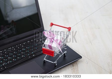 Shopping Cart With Gift Box On Laptop. Concept Of Shopping Online.