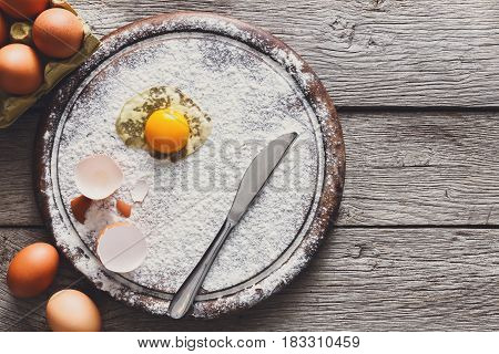 Baking concept. Sprinkled flour and eggs on wooden cutting board near knife, cooking ingredients. Prepare for making yeast dough. Top view, copy space