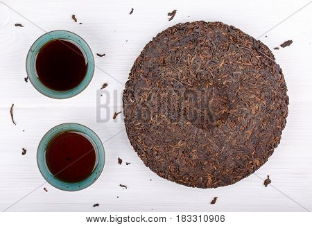 Round flat disc of puer tea and two cup on white. Pressed Chinese fermented Pu-erh tea. Top view.