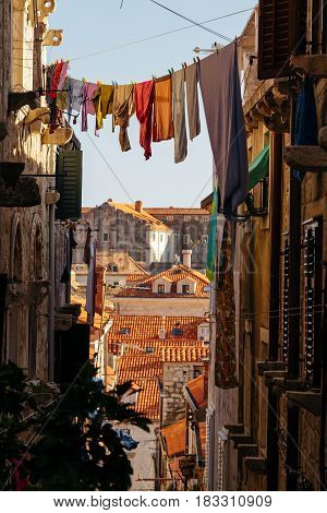 Colorful linen dried on a rope in a narrow European street.