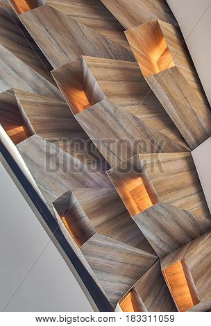 Wooden geometric construction between light walls. There are luminous lamps inside it. Closeup. Vertical.