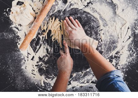 Making homemade noodles on black background, sprinkled wheat flour and cooking hands. Top view on blackboard or table.