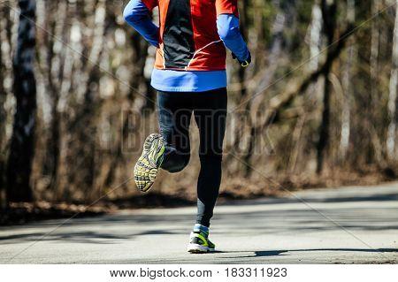 back athletic runner man running asphalt road in city park