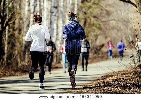 morning run group women running in sunny city park